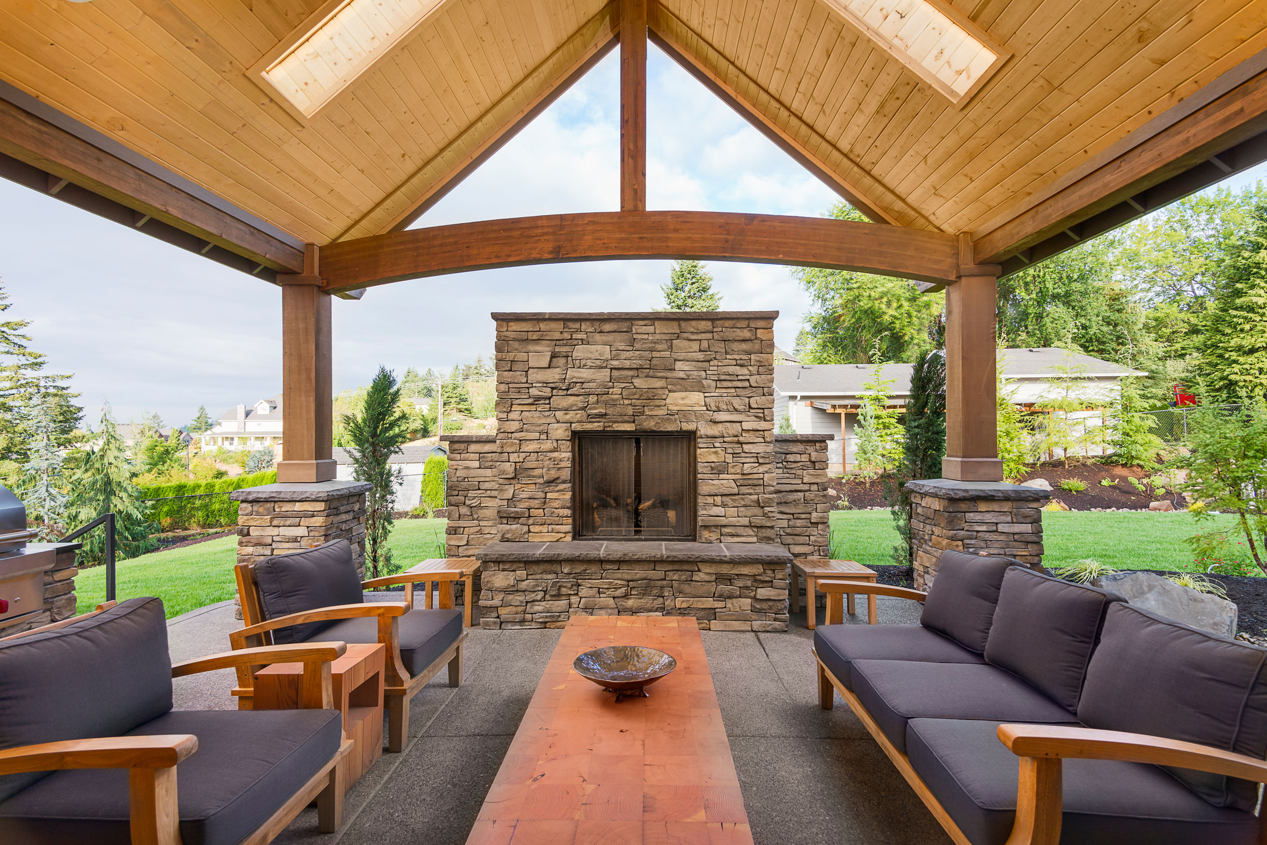 46487571 - covered patio outside luxury home with large stone fireplace, table, and couches