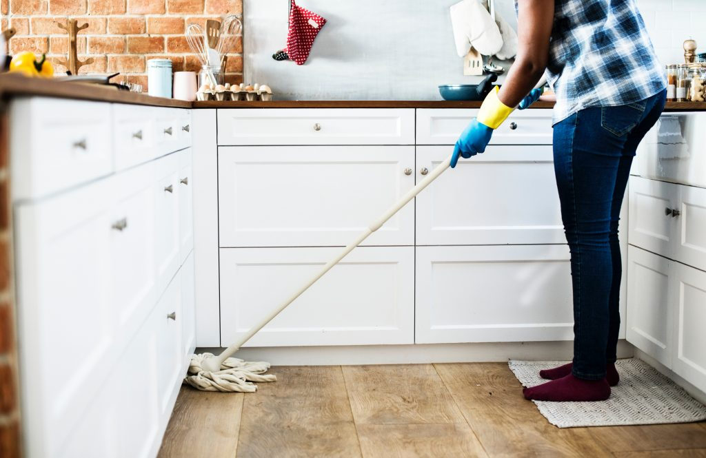 Woman in gloves mopping a floor