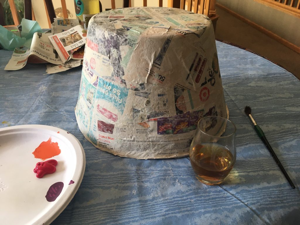 Photo of paper mache gumdrop without paint and glass of whiskey