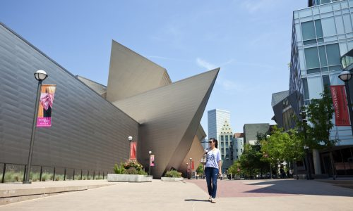 woman walking by the denver art museum summer day