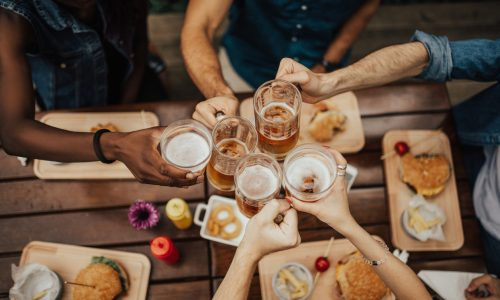 restaurant table with food and friends raising glasses of beer and wine for toast