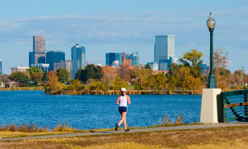 Denver, Colorado, United States - A woman in the foreground jogs near Sloan Lake with the Downtown Denver skyline in the background.