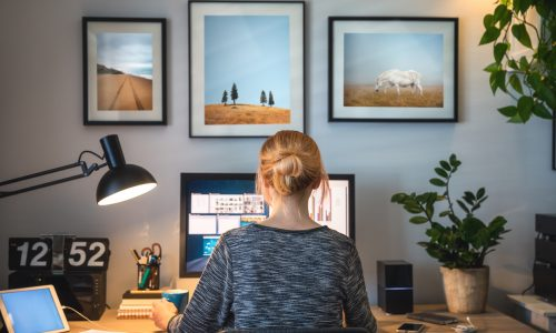 woman-facing-away-from-camera-while-sitting-at-home-office-desk-near-framed-photos-on-wall
