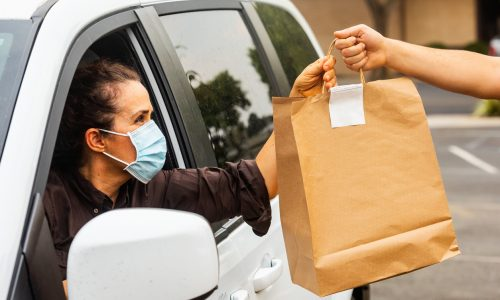 woman-wearing-mask-stretching-arm-out-of-car-to-take-brown-paper-bag-of-take-out-food-from-person-out-of-frame