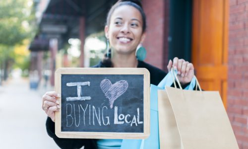 young-woman-smiling-while-holding-brown-paper-bag-and-small-blackboard-sign-reading-I-heart-buying-local