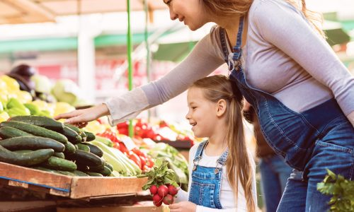 pregnant-mother-wearing-matching-denim-overalls-with-young-daughter-at-denver-farmers-market-vegetable-stand
