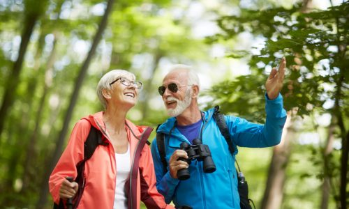 A senior retired couple wearing backpacks and active wear smiling while birdwatching in a Colorado retirement destination.